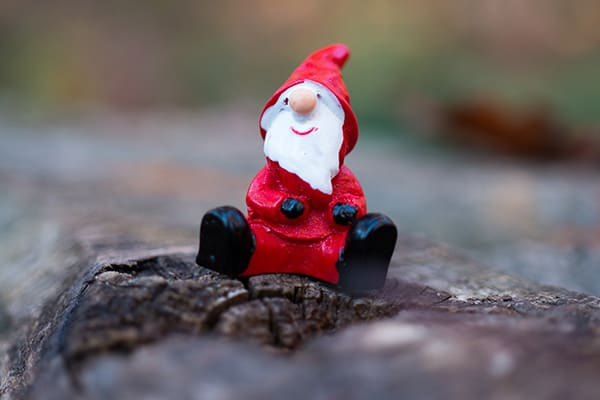 A miniature Father Christmas sitting on a tree trunk.