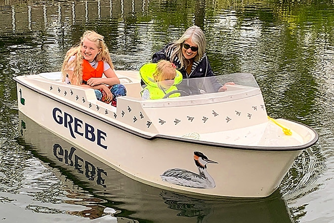 Gillian showing some children the ropes on the lake.